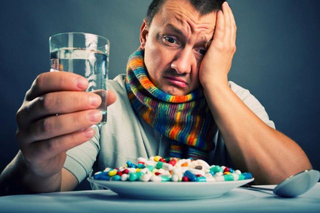 A man with a glass in his hand looking at a plate of pills